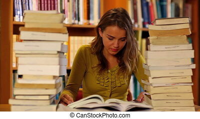 Pretty student studying in the library surrounded by books...