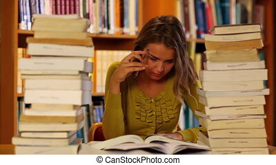 Focused student studying in the library surrounded by books...