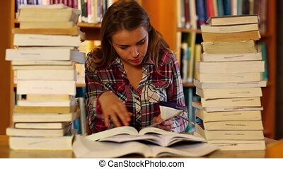 Attentive student studying in the library surrounded by...