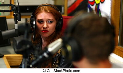 Happy student interviewing someone for radio in the studio...
