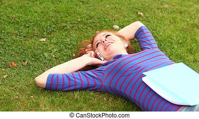 Smiling student lying on grass talking on the phone on...
