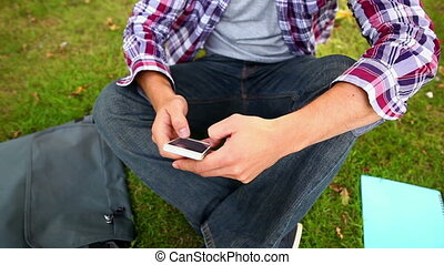 Student sitting on the grass texting on the phone on college...