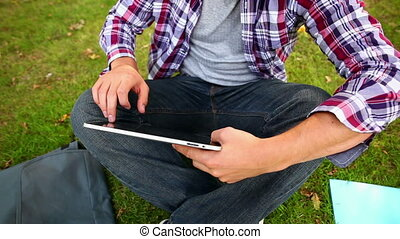 Student sitting on the grass using his tablet on college...