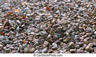 Pebbles falling onto more pebbles in slow motion