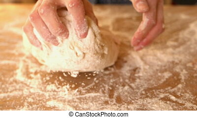 Hands kneading ball of dough on a floury surface in slow...