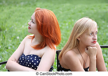 Two beautiful girls sit on bench and take offense at each...