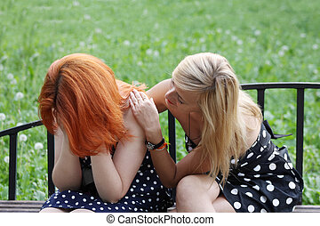 Two beautiful girls sit on bench and one consoles another in...
