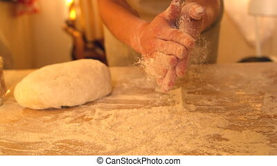 Hands rubbing flour off each other while baking in slow...
