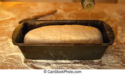 Olive oil being poured over dough in loaf tin on a floury...