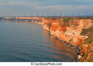 Summer beach on Bulgarian Black sea. Wind power generators
