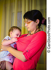 Hungry baby in mother's arms