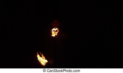 Fire dancer making trails of fire in the dark in slow motion