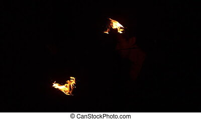 Fire dancer spinning fire in the dark in slow motion