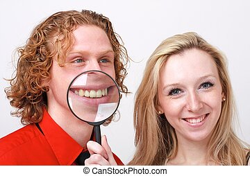smiling couple with magnifying glass - Portrait of young...