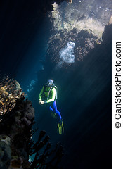 Scuba Diver - a pretty female scuba diver in a cave with...