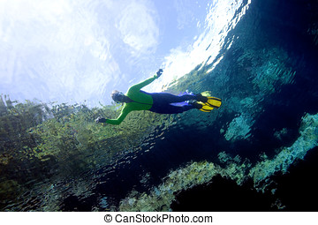 Snorkeller with reflections - a pretty girl, snorkelling....