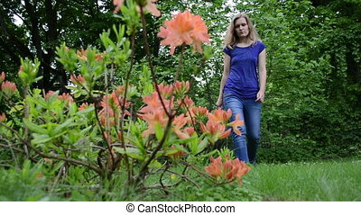 woman rhododendron water - Blond gardener woman water orange...