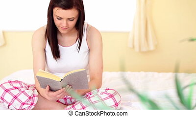 Brunette sitting on the bed reading at home in bedroom
