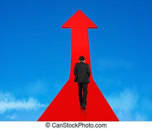 Businessman walking on growing red arrow in sky