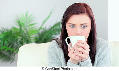 Pretty brunette drinking mug of coffee on the couch in...