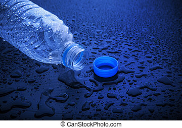 open cap of empty platic bottle lying on dark wet floor