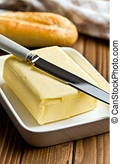 cube of butter with knife on wooden table