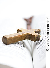 Bible - The Holy Bible with a wooden cross on top of it.