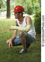 tattooed man in plaster - tattooed man with red helmet and...
