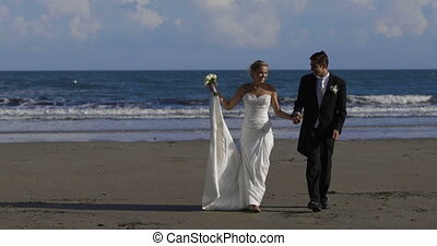 Happy newlywed couple walking on the beach on their wedding...