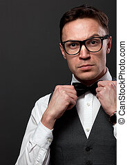Man with beard correcting his bow tie - Fashion photo of a...