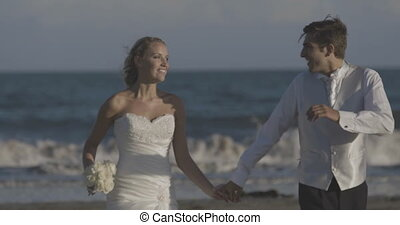 Smiling newlyweds running on the beach on their wedding day