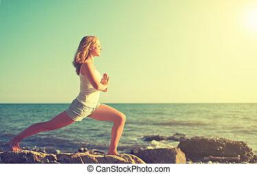 young woman doing yoga on beach - young woman doing yoga on...