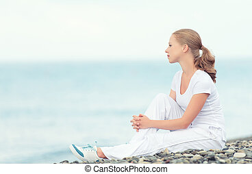 woman in white relax resting on the sea on the beach