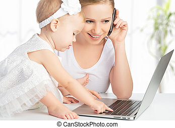 mother with baby daughter works with a computer and phone -...