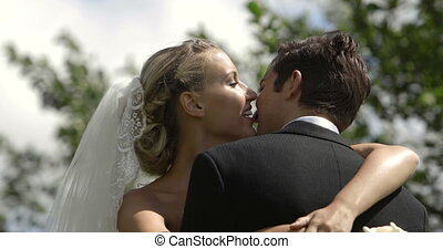 Bride and groom kissing each other outside on their wedding...
