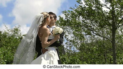 Groom kissing his pretty new wife outside on their wedding...