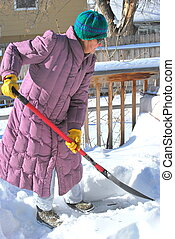 Winter snow. - Mature female shoveling winter snow off her...