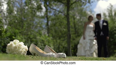Bride and groom walking outside on a sunny day on their...