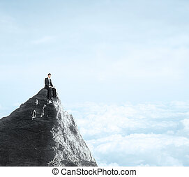 businessman sitting with notebook on top of mountain