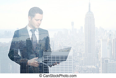 businessman with laptop on city background