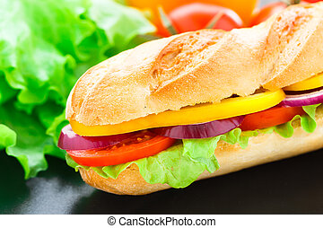 Vegetarian baguette sandwich with lettuce, tomatoes, pepper...