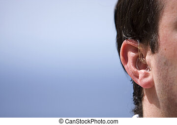 Mans Hearing Aid - Shot of a Mans Hearing Aid against a Blue...