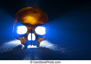 Skull - A scary glowing skull sits on stone surface and...