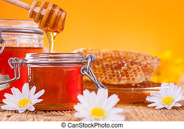 Honey in jar with honeycomb and wooden drizzler -...