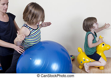 Ball therapy with children - Children do gymnastics on a...