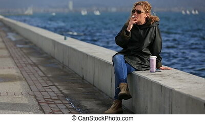 lonely blonde women smoke and drinking coffee at near ocean