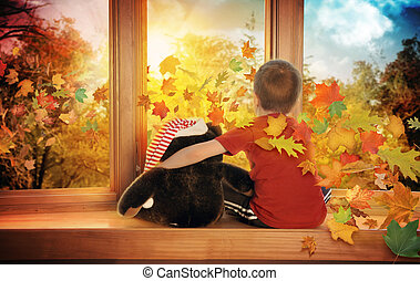 Little Child Watching Fall Leaves in Window - A little boy...