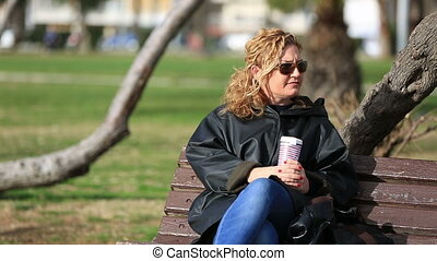 thoughtful blonde women sitting a bank and drinking coffee...