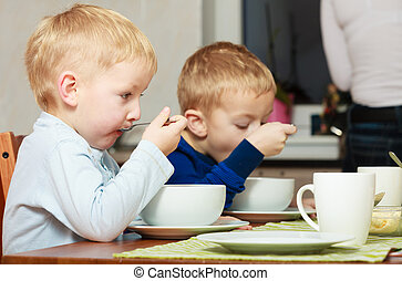 Boys kids children eating corn flakes breakfast meal at the...