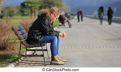 sad blonde women sitting a bank and looking arround at...